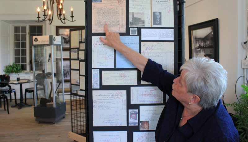 Nancy Gray Lachaîne showing some of the 4000 historical documents and pieces in the exhibit.