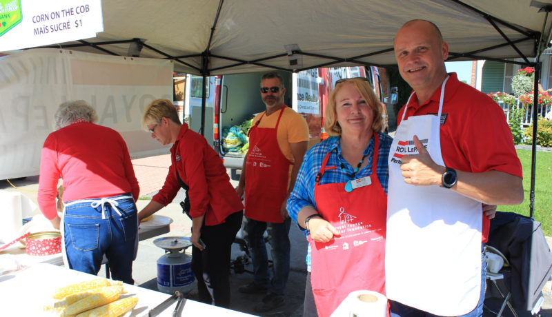 Steven Levac and Nancy Fielding of Royal Lepage Realty serving corn on the cob at their kiosk.