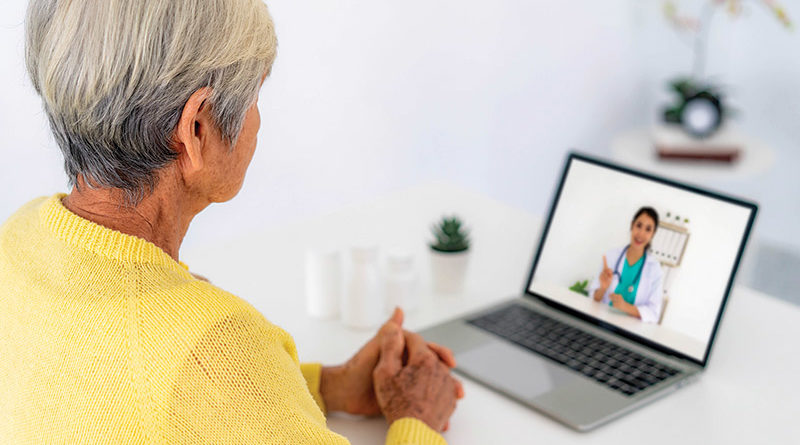 senior lady in yellow sweater who is looking at a portable computer screen with an image of a young female health professional